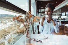 Muchacha negra pensativa en café con la taza de cacao Foto de archivo libre de regalías