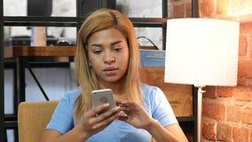 Muchacha negra que hojea Smartphone en el trabajo almacen de video