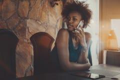 Muchacha negra que llama por teléfono mientras que se sienta en sala de reunión oscura Fotos de archivo libres de regalías
