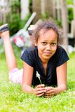 Muchacha negra que miente con la cuchilla de la hierba en prado imágenes de archivo libres de regalías