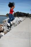 Muchacha negra que salta por el lago imagenes de archivo