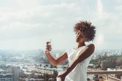 Muchacha negra que toma el selfie en el balcón de la alta subida Imagenes de archivo