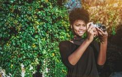 Muchacha negra que usa la leva de la película del vintage en el jardín Fotos de archivo