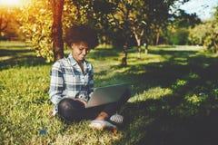 Muchacha negra rizada con el ordenador portátil en parque Imágenes de archivo libres de regalías