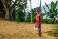 Muchacha nepalesa que juega en un oscilación de bambú tradicional Imagenes de archivo