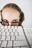 Muchacha Nerdy joven con un teclado Imagen de archivo libre de regalías