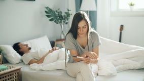 Muchacha nerviosa que se sienta en prueba de embarazo de la tenencia de la cama mientras que individuo que duerme en dormitorio metrajes