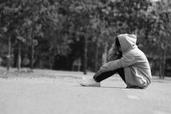 Muchacha nerviosa y sola que se sienta en el camino fotografía de archivo
