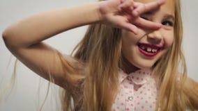 Muchacha, niño, rubios divertidos en una camisa ligera con un modelo rosado del guisante, realizando los movimientos de la danza  metrajes