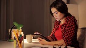 Muchacha o mujer del estudiante con PC de la tableta en el hogar de la noche almacen de metraje de vídeo
