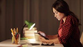 Muchacha o mujer del estudiante con PC de la tableta en el hogar de la noche almacen de video