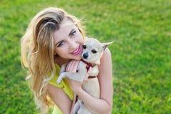 Muchacha o mujer sonriente feliz del encanto que sostiene el perro de perrito lindo de la chihuahua en césped verde en la puesta  Imágenes de archivo libres de regalías