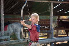 Muchacha o tiroteo lindo de la mujer, del arquero o del cazador con el arco y la flecha el día soleado en la blanco estable en la Fotos de archivo