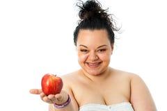 Muchacha obesa joven que sostiene la manzana roja Imagenes de archivo