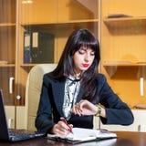 Muchacha ocupada que trabaja en oficina y que mira su reloj Imágenes de archivo libres de regalías