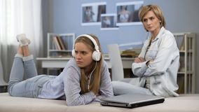 Muchacha ofendida en auriculares que ignora a la momia, conflicto del apego de Internet, relaciones imagenes de archivo