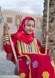 Muchacha omaní joven en un vestido rojo en un oscilación Imágenes de archivo libres de regalías