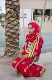 Muchacha omaní joven en un vestido rojo en un oscilación Fotografía de archivo