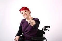Muchacha optimista en silla de ruedas con los pulgares para arriba imagenes de archivo