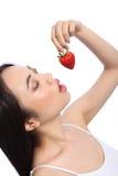 Muchacha oriental atractiva que come la fruta roja de la fresa Fotos de archivo libres de regalías