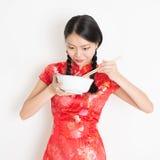 Muchacha oriental en cheongsam rojo que come con los palillos Fotos de archivo