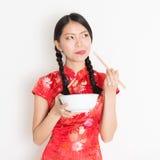 Muchacha oriental en qipao rojo que come con los palillos Foto de archivo