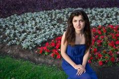 Muchacha oriental hermosa que se sienta en flores imagen de archivo libre de regalías