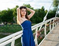 Muchacha oriental joven hermosa en el puente sobre el río imagenes de archivo