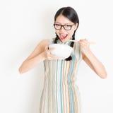 Muchacha oriental que come con los palillos Foto de archivo libre de regalías
