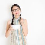 Muchacha oriental que come con los palillos y el pensamiento Imagen de archivo libre de regalías