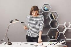 Muchacha oscuro-cabelluda apuesta hermosa joven en la camisa rayada que coloca la tabla cercana en lugar de trabajo cómodo en cas foto de archivo libre de regalías