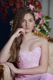 Muchacha oscuro-cabelluda hermosa en el vestido de noche rosado que se sienta en una silla Imágenes de archivo libres de regalías