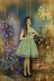 Muchacha oscuro-cabelluda hermosa que hace una pausa la chimenea Imagen de archivo libre de regalías