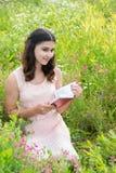 muchacha Oscuro-cabelluda que lee un libro en la naturaleza Fotografía de archivo libre de regalías