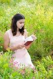 muchacha Oscuro-cabelluda que lee un libro en la naturaleza Foto de archivo libre de regalías