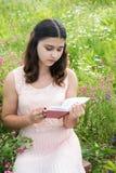 muchacha Oscuro-cabelluda que lee un libro en la naturaleza Foto de archivo