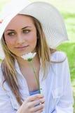 Muchacha pacífica joven que sostiene una flor blanca en un parque Imagenes de archivo