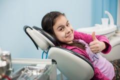 Muchacha paciente feliz que muestra los pulgares para arriba en la oficina dental Concepto de la medicina, de la estomatología y  fotografía de archivo