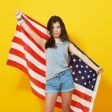 Muchacha patriótica adolescente alegre con la bandera de los E.E.U.U. Foto de archivo libre de regalías