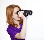 Muchacha pelirroja adolescente con los prismáticos Imagenes de archivo