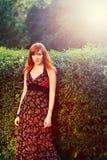 Muchacha pelirroja atractiva en un parque del verano Foto de archivo