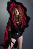 Muchacha pelirroja atractiva que presenta en traje del diablo Foto de archivo libre de regalías