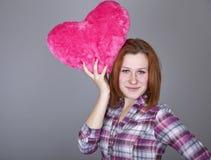Muchacha pelirroja con el juguete del corazón. Imagen de archivo libre de regalías