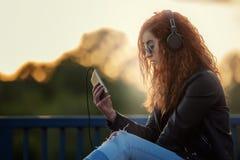 Muchacha pelirroja con el teléfono Imágenes de archivo libres de regalías