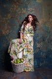 Muchacha pelirroja con una cesta de manzanas imagen de archivo libre de regalías