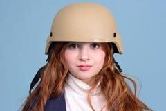 Muchacha pelirroja en el casco militar Imagenes de archivo