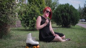 Muchacha pelirroja en el vestido negro que se coloca en la acera en frente metrajes