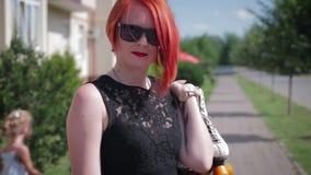 Muchacha pelirroja en el vestido negro que se coloca en la acera en frente almacen de video