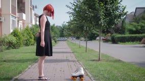 Muchacha pelirroja en el vestido negro que se coloca en la acera en frente almacen de metraje de vídeo