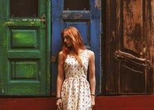 Muchacha pelirroja en la calle fuera de puertas de madera Fotografía de archivo libre de regalías
